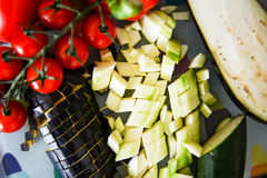 Fresh Raw Vegetables. Plum baby tomatoes, pepper, paprika, onion, courgettes, eggplant cut into pieces Stock Image