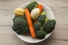 Fresh raw vegetables. Porcelain bowl with fresh raw broccoli, onion, potato and carrots as ingredients for cooking on wooden board Stock Photography