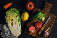 Fresh raw vegetables on a rustic background - Peking cabbage, pepper, tomato, cucumber, lemon, garlic. The concept of healthy eati. Ng. Vegetarian food, top view Stock Photography