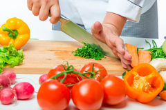 Fresh raw vegetables for salad and chef hands with a knife Royalty Free Stock Images