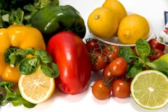 Fresh raw vegetables for the preparation of vegetarian meals. Fresh raw vegetables, salad preparation, pepper tomatoes cucumber fresh salad lime lemon cheese Royalty Free Stock Photos