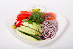 Fresh raw vegetables. Fresh raw sliced vegetables and herbs on white plate Stock Photos