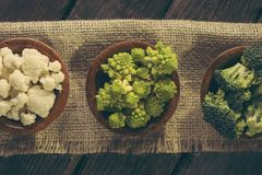 Fresh raw vegetables. Table top shot of fresh pieces of Romanesco broccoli, broccoli and cauliflower in small rustic wooden bowls Stock Photography