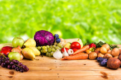 Fresh raw vegetables. Various colorful raw vegetables on the wooden table with green background Royalty Free Stock Images