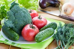Fresh raw vegetables. On white plate on wooden table, eggplant, onion and knife on background Stock Photo