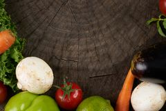 Fresh raw Vegetables on wooden stump. Bio Healthy food, herbs, spices, Carrots, aubergine, lettuce, tomato, mushrooms, Bulgarian pepper.  Organic vegetables on Royalty Free Stock Photo