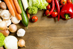 Fresh raw vegetables on a wooden table. Fresh raw vegetables cabbage carrot onion tomato cucumber pepper mushroom garlic cabbage salad on a wooden table top view Stock Image