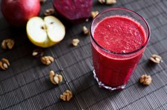 Fresh raw vegetarian autumn red smoothie made from beetroot, carrot, apple and walnuts on the dark, wooden background. Fresh raw vegetarian red smoothie made Royalty Free Stock Photography