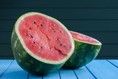 Fresh raw watermelon with seeds cut in halves on blue background Stock Image