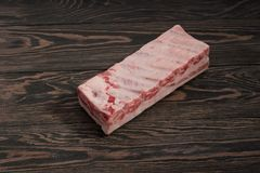 Fresh raw whole rack of pork loin with ribs on a dark wooden background. Fresh raw whole rack of pork loin with ribs on a dark wooden table Stock Image