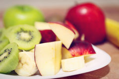 Fresh raw whole and sliced apple and kiwi closeup, gently toned, soft focus Stock Images