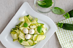 Fresh raw zucchini salad with basil and mozzarella wooden backgr. Fresh zucchini and leaves of basil Stock Photo