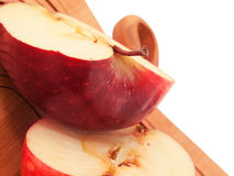 Fresh, red apple cut in half on a wood cutting board. macro Royalty Free Stock Photos