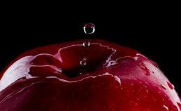 Fresh red apple with droplets of water against black background reflection drops Stock Photos