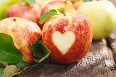 Fresh red apple with heart cutout. Fresh red apple on an old textured weathered wooden table with a heart cutout royalty free stock images