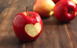 Fresh red apple with a heart shaped cut-out. On wooden background Royalty Free Stock Photography