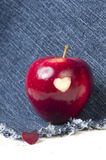 Fresh red apple with a heart shaped cut-out on jeans background. Stock Images