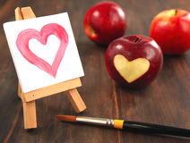 Fresh red apple with a heart shaped cut-out and painted heart. On wooden table Stock Photos