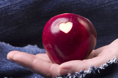 Fresh red apple with a heart shaped cut-out in woman hand on den Stock Photo