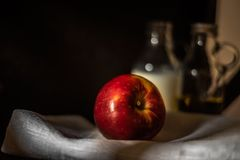 Fresh red apple on linen fabric with blurred glass bottles background royalty free stock images