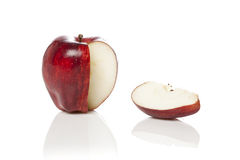 A fresh red apple with a slice cut out. On a white background Stock Photography