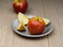 Fresh red Apple sliced on a plate spotted natural wooden background Royalty Free Stock Images