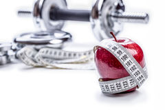 Fresh red apple, tape measure, and in the background Fitness dumbbells. Royalty Free Stock Photo