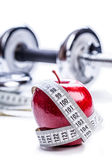Fresh red apple, tape measure, and in the background Fitness dumbbells. Royalty Free Stock Images