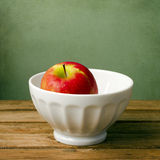 Fresh red apple in white bowl Royalty Free Stock Images