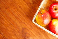 Fresh red apples in basket over wooden background.  Free space for text . Top view Stock Photos