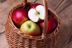 Fresh red apples in basket over wooden background Royalty Free Stock Photography