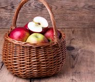 Fresh red apples in basket over wooden background Royalty Free Stock Image