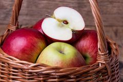 Fresh red apples in basket over wooden background Stock Images