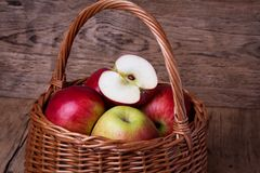 Fresh red apples in basket over wooden background Stock Image