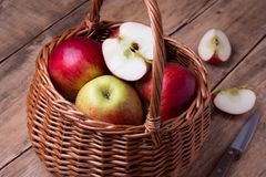 Fresh red apples in basket over wooden background Stock Photos