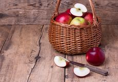 Fresh red apples in basket over wooden background Royalty Free Stock Photos