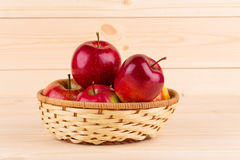 Fresh red apples in basket on wood. Stock Photography