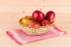 Fresh red apples in basket on wood. Royalty Free Stock Photography