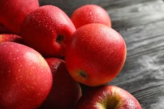 Fresh red apples with drops of water on wooden table. Closeup Royalty Free Stock Image
