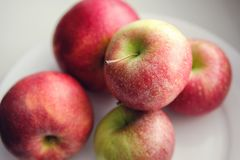Fresh red apples on a white plate. Healthy diet royalty free stock image