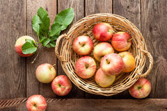 Fresh red apples in wicker basket on wooden table. Royalty Free Stock Photo