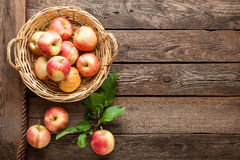 Fresh red apples in wicker basket on wooden table. Royalty Free Stock Photography