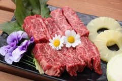 Fresh red beef with sliced pineapple and flowers on black plate. Deliciously Stock Photography