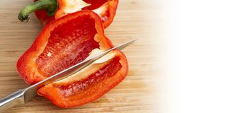 Fresh red bell pepper being cut by sharp stainless knife, wide b Stock Photography