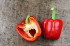 Fresh red bell pepper capsicum and a cut one. On a grungy metal background stock photo