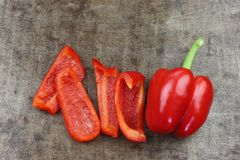 Fresh red bell pepper capsicum and some cut pieces. On a grungy metal background royalty free stock photos