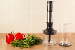 Fresh red bellpepper with herbs and a blender on kitchen table Stock Photo