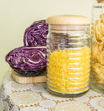 Fresh red cabbage cut in half and jars with pasta Royalty Free Stock Photo