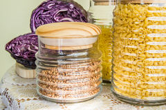 Fresh red cabbage cut in half and jars with pasta and buckwheat Stock Photos