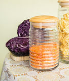 Fresh red cabbage cut in half and jars with pasta and red lentils Stock Photos